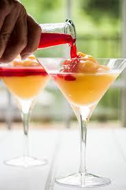 peach bellini slush in a martini gl pouring the homemade raspberry liqueur on the frozen peach slush