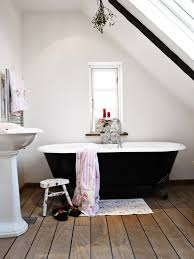 small clawfoot tub. A Simple And Modest Space, This Bathroom Features Black Clawfoot Tub Sitting Atop Small