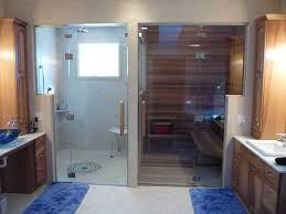 glass door wall and transom installation for shower room and sauna back to back sauna and steam room shown in lower light