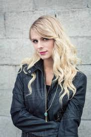 young blonde haired woman in front of breeze block wall wearing leather jacket looking at smiling