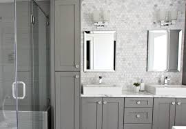 hexagon shape are used in this double cabinet style vanity bathroom s backsplash while the countertop is of statuario marble gray cabinets and drawers