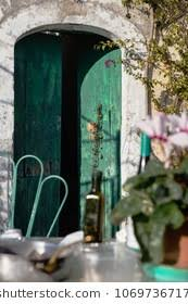 green wooden door ajar old country house with a dining table and a chair in