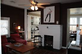 stylish ceiling fan with lights over wooden tail table and white fireplace mantle in dark living room paint ideas