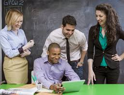 what does business casual attire mean four coworkers looking at a laptop dressed in business casual attire
