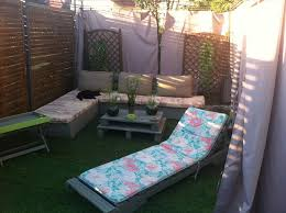 decorate simple diy pallet patio furniture with flowery lather and cream cushions beside wooden wall