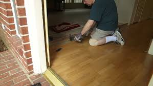 a workman or homeowner handyman type engaged in a diy project of removing old laminate flooring in preparation of new floor covering