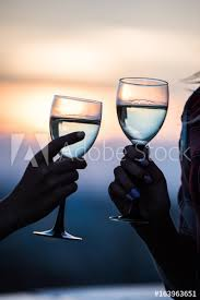 two female friends clinking wine glasses close to the sea during the sunset summer lifestyle concept glasses of wine in the hands of women