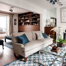 decorating a large living room. Open-plan Living Room With White Walls, Neutral Sofa, Blue Rugs, Cushions And Glass Coffee Table Decorating A Large