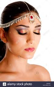 beautiful face of a middle eastern woman with arabic style makeup and head jewelry typacally used by indian belly dancers isolated