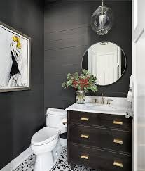 dramatic black plank walls are complemented with black and white cement floor tiles fixed beneath a dark brown oak vanity fitted with vintage brass pulls