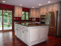 red kitchen wall paint color with black granite countertops and white cabinet