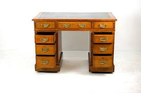this desk has fine pierced brass drop handles and solid mahogany drawer linings good original dark leather and original metal and pot castors