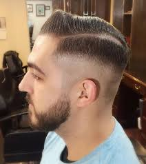 a barbershop photograph of a male hipster with a side quiff hairstyle and an executive haircut