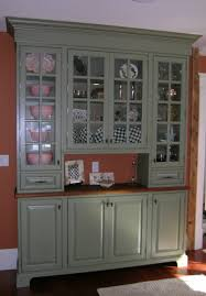 pale grey wooden pantry cabinet with 4 clear glass doors and two drawers on dark wooden floor plus orange wall