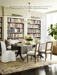 a cream gray and taupe oushak rug contrasts with a dark brownish black lacquered floor and plements white walls and dark wood tones in the dining room