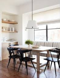 light wood dining table surrounded by sleek black chairs under a white drum hanging light