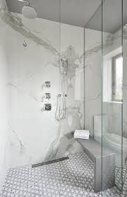 mosaic bathroom tiles continue into a seamless glass shower fitted with two polished nickel shower heads mounted to a calcutta ora marble slab surround