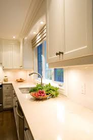 cool kitchen design with teslin hanstone countertop matched with white  cabinets plus sink with silver faucet