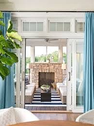 the porch is basically an additional living room with a fireplace outdoor lamps comfortable chairs a rug i want one