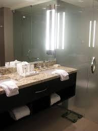 bathroom wood vanity. bathroom wooden storage wall diagonally tile floor floating vanity white marble countertop recessed lights wood