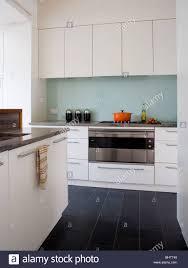 black floor tiles in modern white kitchen with glass splashback behind stainless steel oven tile w9 floor
