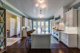 the elongated kitchen features a dual sink center island on a hardwood flooring decorative ceiling is lighted by pendant lights