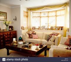 Window In Living Room Cream Sofa With Patterned Cushions Below Window In Living Room