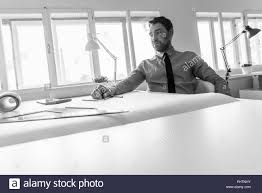 architect office supplies. Architect Sitting At Desk With Large Sheet Of Paper And Office Supplies. Architect Supplies P