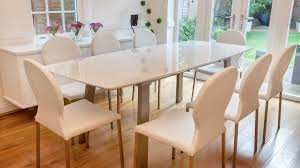 large white extending dining table and comfortable dining chairs