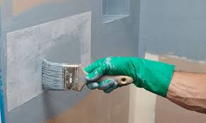 man painting waterproofing on shower walls