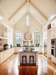 high modern vaulted ceiling kitchen lighting ideas with brown laminate floor tiles white cabinets and lighting extension