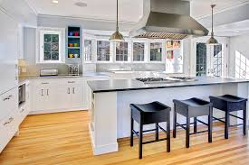 white kitchen with black wooden bar stools and light wood flooring kitchen with modern pendant