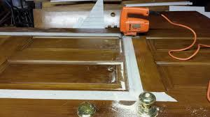 to insert decorative glass into your plain front door cut out the area with a jigsaw