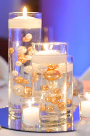 The centerpieces included vases of varying heights filled with gold and  white pearls and topped with floating candles.