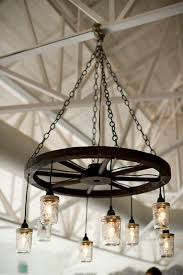 wagon wheel chandeliers are gorgeous lighting for a barn wedding or rustic theme