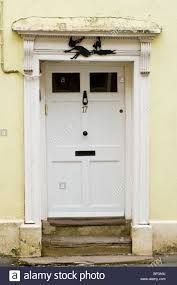 white painted wooden paneled front door no 17 with knocker letterbox flat pediment and architrave of town house in uk