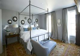 elegant bedroom with blue walls paint color iron canopy bed collection of black convex mirrors blue settee daybed yellow red oriental rug and gray sik