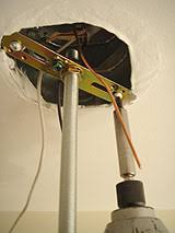 Installing light fixture mounting bracket to junction box.
