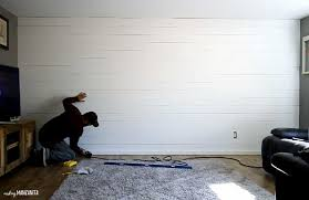 a man reinstalling the baseboard of a wall after all the shiplap has been attached