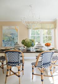 charming dining room boasts serena lily chevron riviera side chairs placed on whitewashed wood floors surrounding a two tone x based dining table lit by