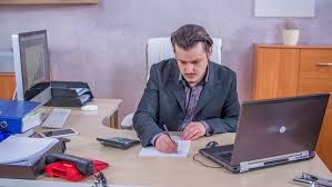 wide angle view busy design office. a businessman is calculating something and then he writing things down on piece of wide angle view busy design office s