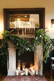 fireplace decorated with lush greenery birch logs and candle holders