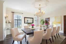 black dining table with ivory velvet dining chairs and yellow abstract art