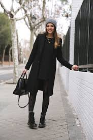 natalia cabezas is wearing a black dress and coat from zara boots from dr