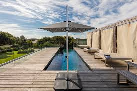 aurora 2 8m square cantilever umbrella on weighted base next to pool