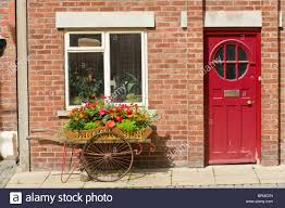 red painted front door window and flower display in barrow outside brick built house in llandrindod wells powys mid wales uk