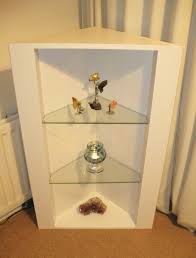 triangular corner shelf unit painted white with two glass shelves