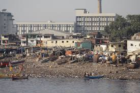 poverty and urbanisation global education slum housing is built along the polluted river while modern housing is further away in