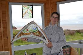 the first sea glass mosaic she ever created hangs in the background as jackie trimper displays