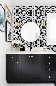 black and white bathroom with vase of flowers small gallery wall round mirror